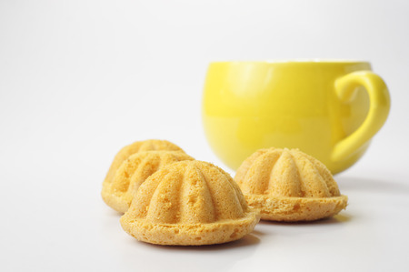 Hot cup of coffee with bahulu, traditional malay sponge cake
