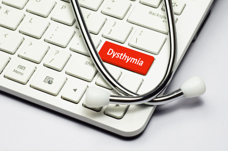 major depression: Dysthymia text, stethoscope lying down on the computer keyboard