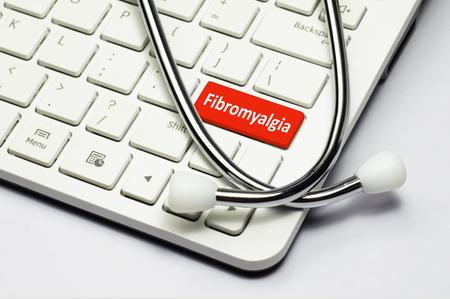 symptom: Fibromyalgia text, stethoscope lying down on the computer keyboard Stock Photo