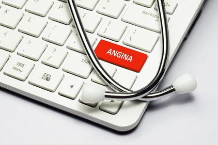 angor: Texto Angina, estetoscopio tumbado en el teclado de la computadora Foto de archivo