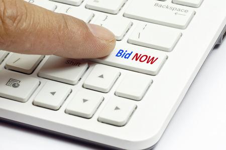 puja: Dedo pulsador Puja Ahora en el teclado blanco - concepto de negocio Foto de archivo