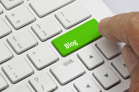 Finger pushing the green button of keyboard with Blog word - Business Concept Фото со стока
