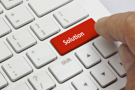red button: Finger pushing the red button of keyboard with solution word - Business Concept Stock Photo