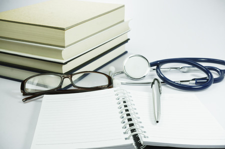 clean lungs: Stack of book, stethoscope, glasses, notebook and pen isolated on white background
