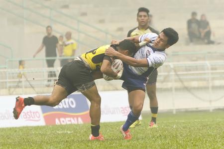 defeated: KELANA JAYA, SELANGOR - OCT: Perak rugby palyer(L) tackled by Sabah players. Sabah defeated Perak with score Sabah 28 - Perak 16, in Kelana Jaya, Malaysia on October 3rd, 2015 Editorial