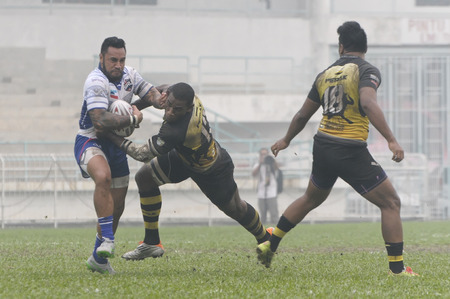 defeated: KELANA JAYA, SELANGOR - OCT: Orene Aii of Sabah (L) tackled by Perak players. Sabah defeated Perak with score Sabah 28 - Perak 16, in Kelana Jaya, Malaysia on October 3rd, 2015 Editorial