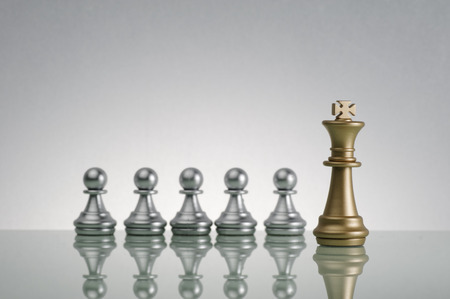 Golden King and silver pawn on chess game - Leadership Concept