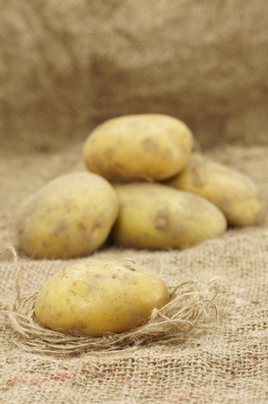Close up of Potatoes lying on the top of hessian Stock Photo