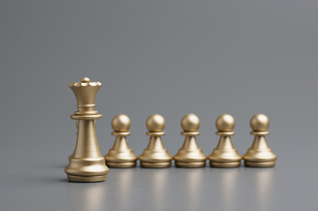 Golden Queen with his pawn on the board Stock Photo
