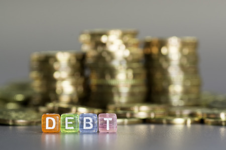 creditor: Debt text on colorful dice and the gold coin on the background