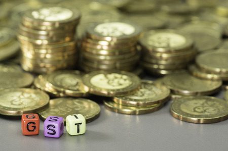 GST or Good and Services Tax word written on colorful dice and gold coins in the background Banque d'images