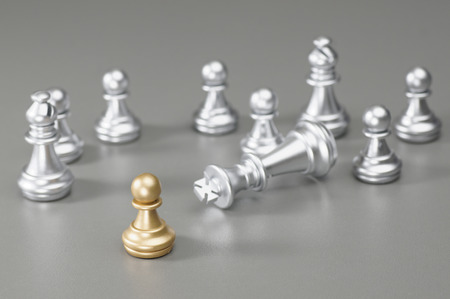 pawn to king: Golden pawn take down the silver King on the board Stock Photo