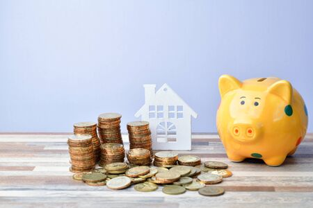 Close up of Wooden home, piggy bank and stack of money coins, Business concept Stock Photo