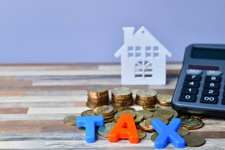 Close up of TAX word on wooden home and stack money coins on the backrgound.