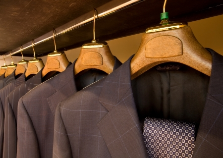 tweed: A row of designer suits hanging in a menswear store. Stock Photo