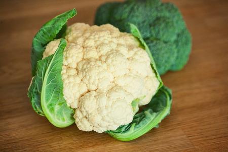 head of cauliflower: Cauliflower and broccoli on the wooden board