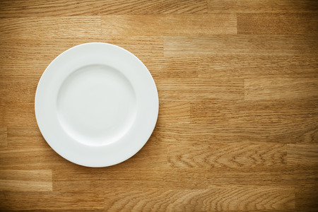 empty surface: Empty white plate on wooden table