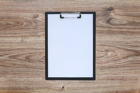 clipboard: Blank white paper sheet in a clipboard on wooden table. Template.