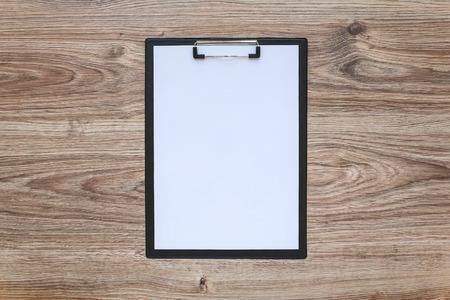 Leeg wit vel papier in een klembord op houten tafel. Sjabloon.