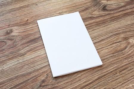 Blank van de brochure is op een houten bureau. Sjabloon voor uw ontwerp.