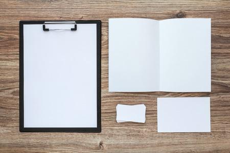 portapapeles: Modelo de la identidad corporativa encuentra en el escritorio de madera. Papel del asunto maqueta con el sobre, tarjeta, etc. Vista superior. Foto de archivo
