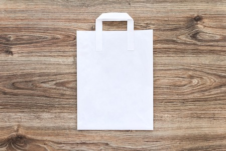 Blank of paper shopping bag on the wooden background. Mock up for your design 免版税图像