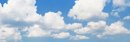 Background of Light blue sky with fluffy clouds. Horizontal panorama