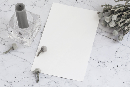 Blank sheet of paper on marble with brunia flowers and candle. Mockup for calligraphy lettering. Mockup for lettering and design.