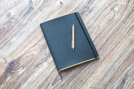 Closed classic planner with pen is on a wooden desk. Nothing extra 免版税图像