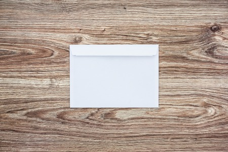 Blank white envelope on wooden background. Template for your design. Mockup object