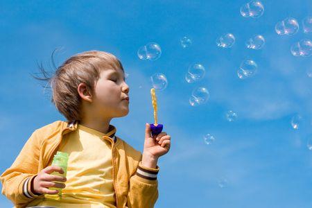 Boy blowing bubbles Фото со стока