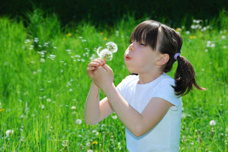 girl blowing: Girl Blowing Dandelion Seeds Stock Photo