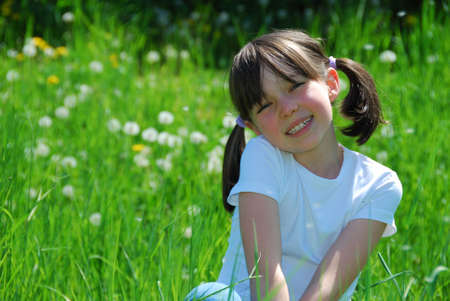 Happy girl sat in field
