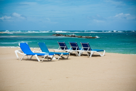 calm beach with deckchairs under the blue sky photo