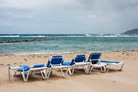 group of deckchairs on the calm beach photo