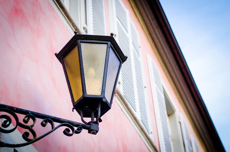 vintage street lamp on red and pink house photo