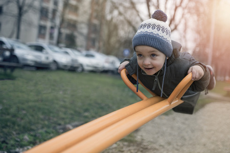 Adorable little 2-3 year old boy having fun on playground, child wearing blue hoody jacket and blue cap