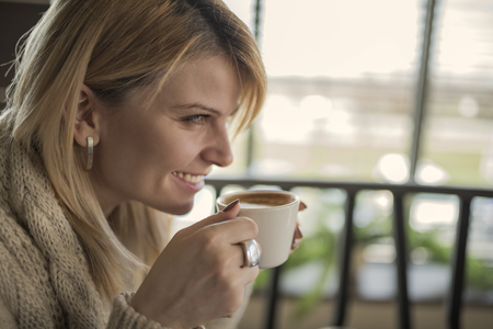 Portrait of young woman drinking cup of coffee and enjoying her leisure time. Business woman drinking coffee in cafe during her work break. Enjoying the moment and delicious sip of coffee.