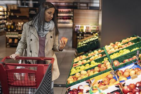 Housewives, women with shopping cart in supermarket. Gorgeous young woman with a shopping cart looking at some products on a supermarket aisle. Woman in the supermarket. Beautiful young woman shopping in a supermarket and buying fresh organic vegetables. Standard-Bild