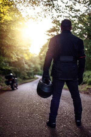Motorcycle guy in raiders clothes, gearing up. A young men stands near an motorcycle in nature during sunset. Biker with motorcycle on the road. Motorcycle and safe driving. Helmet and motorcycle. Standard-Bild