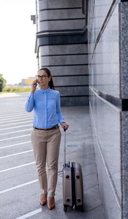 Young attractive woman walking and using a smart phone on a city street. Pretty smiling female flight attendant carrying baggage going to airplane, in the airport.