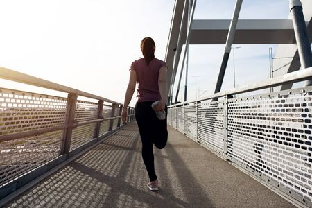 Sunset exercise with beautiful, sport woman. Female runner listening to music while jogging