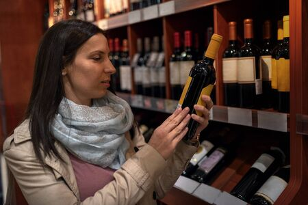 Portrait of happy young woman holding wine bottle in hands and smiling while standing in liquor store. Happy young woman choosing and buying wine in market. Sale, shopping, consumerism and people concept.