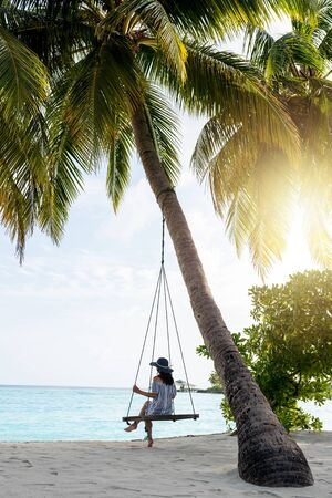 Young beautiful woman relaxing in swing hanging on coconut palm at exotic beach. Blue sea and white sand. Fashion girl enjoying on seashore. Portrait of young brunette relaxing on the beach.