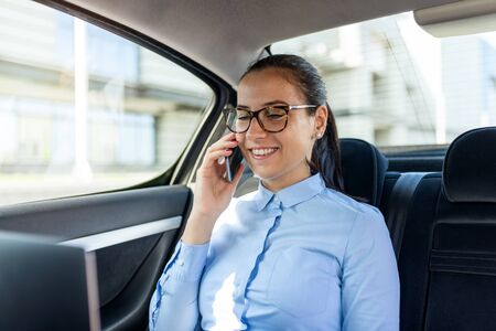 Business woman sitting in the car and talking on the cell. Businesswoman in a car on the phone. Beautiful business woman in the car.Business and lifestyle concept. Standard-Bild