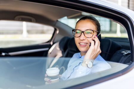 Attractive young woman on the business trip, taking a coffee break. Attractive business woman with phone in the back seat of the car. Close up portrait of a young business woman. Standard-Bild