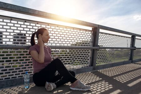 Sunset exercise with beautiful, sport woman. Woman fitness jogging, workout wellness concept. Female runner listening to music while jogging