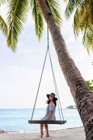 Beautiful fit girl on travel vacation. Portrait of smiling and attractive young woman at sea. Young beautiful woman relaxing in swing hanging on coconut palm at exotic beach. Standard-Bild - 143168927