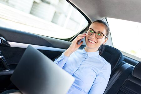 Business woman sitting in the car and talking on the cell. Businesswoman in a car on the phone. Beautiful business woman in the car. Business and lifestyle concept.