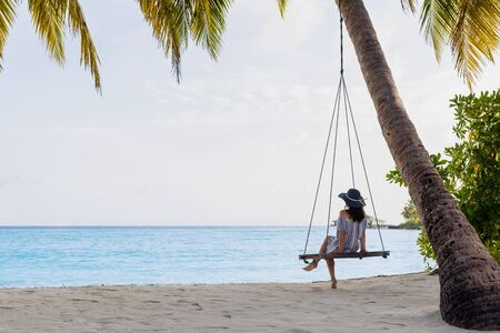 Beautiful fit girl on travel vacation. Portrait of smiling and attractive young woman at sea. Young beautiful woman relaxing in swing hanging on coconut palm at exotic beach. Standard-Bild